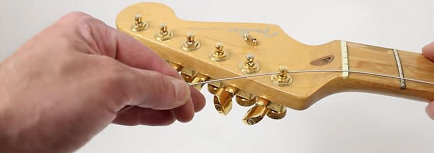 Coloca las cuerdas en las clavijas de tu guitarra eléctrica