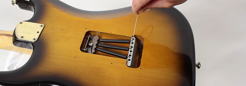 Coloca las cuerdas en el puente de la guitarra eléctrica
