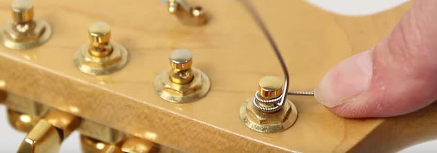 Enrolla con un nudo las cuerdas en las clavijas de tu guitarra eléctrica