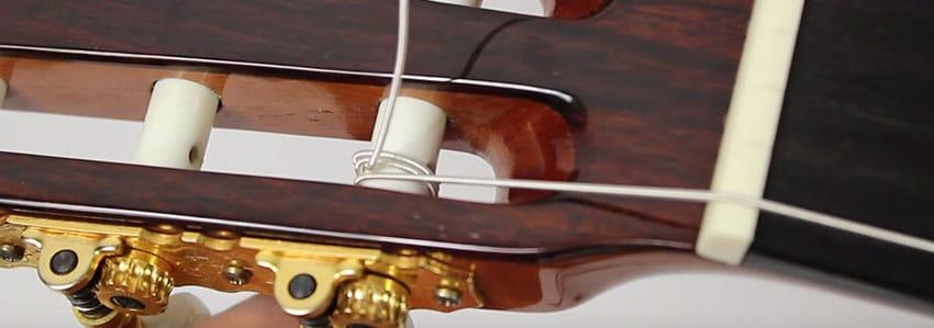 Apretamos las clavijas para ajustar las cuerdas de una guitarra clásica