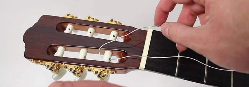 Inserta la cuerda de nylon en la clavija de tu guitarra clásica
