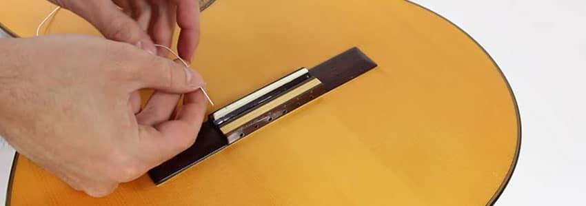 Insertar cuerda de nylon en el puente de una guitarra clásica
