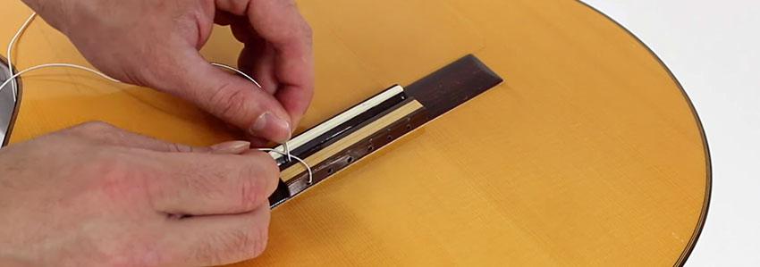 Cómo hacer un nudo a una cuerda de nylon para poner cuerda de guitarra clásica