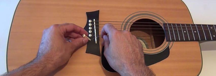 Aprieta el pivote para cambiar las cuerdas de una guitarra acústica