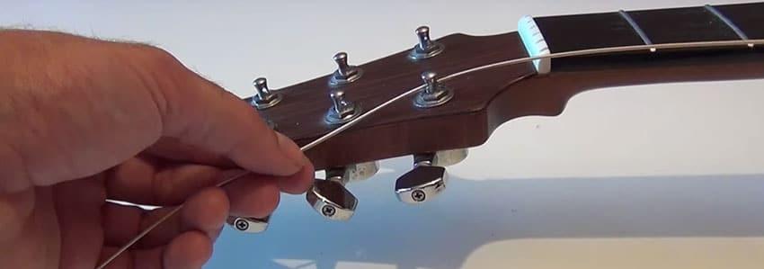 Coloca las cuerdas en las clavijas de tu guitarra acústica