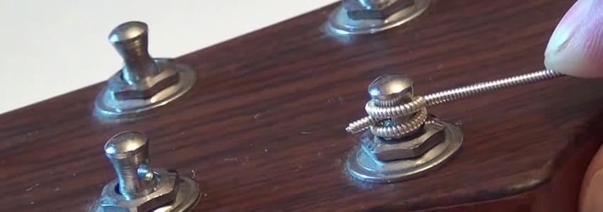 Enrolla con un nudo las cuerdas en las clavijas de tu guitarra acústica